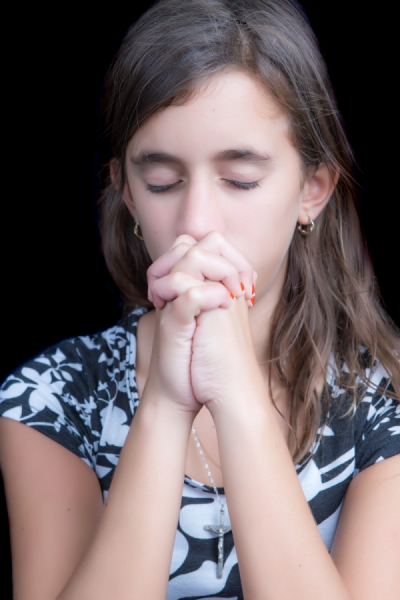 Cute girl praying with her eyes closed (isolated on back)